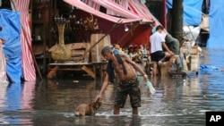 Seorang pria mengelus seekor anjing di sepanjang jalan yang tertutup banjir akibat hujang yang ditimbulkan Topan Nock-Ten (26.12). Quezon City, Utara Manila, Filipina. (foto: AP Photo/Aaron Favila)