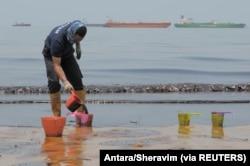 Seorang polisi menyendoki minyak yang mencemari Pantai Banua Patra dari tumpahan minyak di perairan Balikpapan, Kalimantan Timur, 2 April 2018. (Foto: Antara/Sheravim via REUTERS)