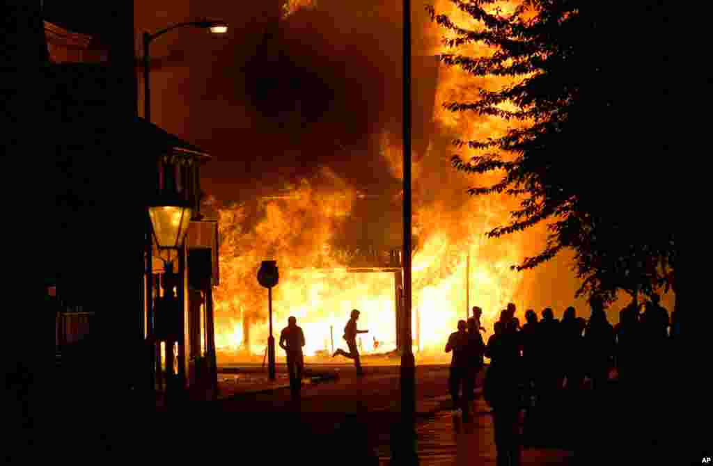 August 8: A shop is in flames as rioters gather in Croydon, south London.. Violence and looting spread across some of London's most impoverished neighborhoods, with youths setting fire to shops and vehicles, during a third day of rioting in the city that