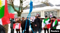 "FILE - Iranian exiles shout slogans in front of a mock gallows to protest against executions in Iran during a demonstration outside the Iranian Embassy in Brussels, Dec. 29, 2010. Iran researcher Raha Bahreini said June, 27, 2018, that said Amnesty International was outraged that Iranian authorities had not taken steps to end what she called the ""horrendous practice of executing juvenile offenders."""