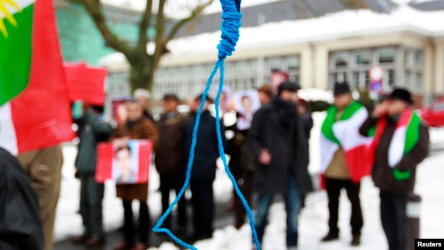 FILE - Iranian exiles shout slogans in front of a mock gallows to protest against executions in Iran during a demonstration outside the Iranian embassy in Brussels, Dec. 29, 2010.