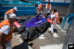 Course officials remove the (37) DS Virgin car driven by Alex Lynn off the track after coming to a stop during Formula E New York City ePrix all-electric auto race, July 16, 2017, in the Brooklyn borough of New York.