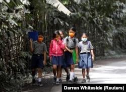 Anak-anak sekolah memakai masker saat berjalan di daerah yang terkena abu vulkanik dari Gunung Agung di dekatnya, di Kabupaten Karangasem, Bali, 29 November 2017. (Foto: REUTERS/Darren Whiteside)