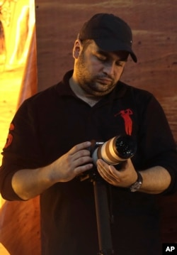 FILE - Jawad Nasrallah, the second-eldest son of Hezbollah leader Sheikh Hassan Nasrallah, adjusts his camera during a speech by his father, in suburban Beirut, Lebanon, Nov. 3, 2014. Jawad has been designated by the U.S. State Department as a global terrorist.