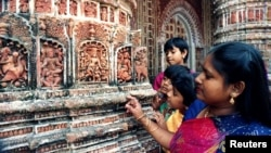 FILE - Visitors at Kantajir Mandir, one of Bangladesh's oldest Hindu temples, examine thousands of clay idols and historic images on the temple's walls. Photo taken July 1995. Ten people were hurt in bomb blasts at the temple, Dec. 5, 2015.