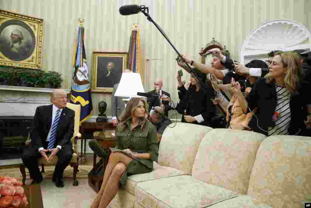 First lady Melania Trump listens as her husband President Donald Trump speaks to reporters during a meeting with Argentine President Mauricio Macri his wife Juliana Awada in the Oval Office of the White House.