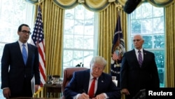 U.S. President Donald Trump signs an executive order imposing fresh sanctions on Iran as Treasury Secretary Steven Mnuchin and Vice President Mike Pence look on in the Oval Office of the White House in Washington, U.S., June 24, 2019. REUTERS/Carlos Barria