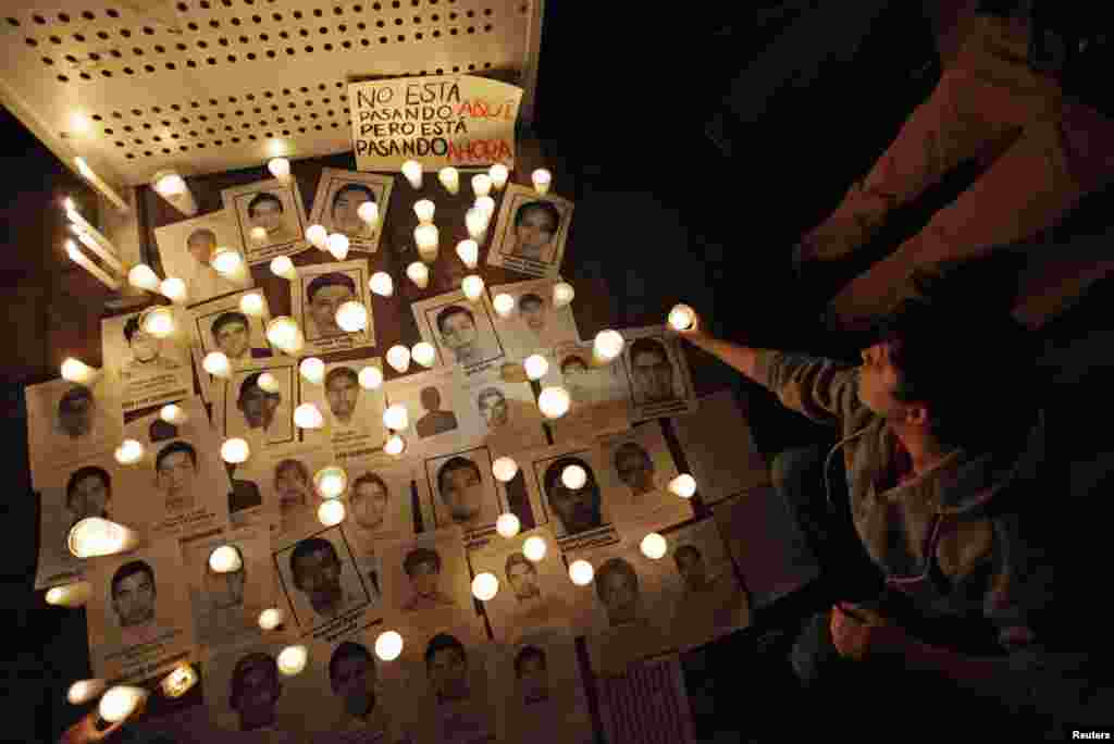 People light candles around the photographs of missing students from the Ayotzinapa teachers' training college during a protest at the Monterrey Institute of Technology in Monterrey, Oct. 23, 2014.