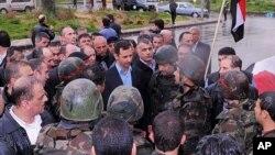2013年7月31日,阿萨德(中)与在霍姆斯省的叙利亚士兵见面。(资料图片)