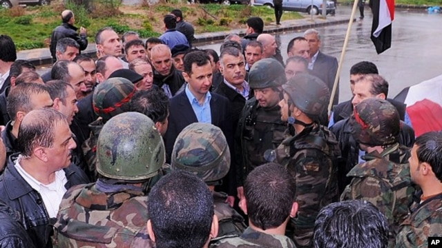 This July 31, 2013, screen grab from the official Instagram account of the Syrian Presidency purports to show Bashar Assad visiting with soldiers in Baba Armr, Homs province, Syria, in 2012.