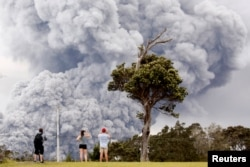 People watch as ash erupts from the Halemaumau crater near the community of Volcano during ongoing eruptions of the Kilauea Volcano in Hawaii, U.S., May 15, 2018.