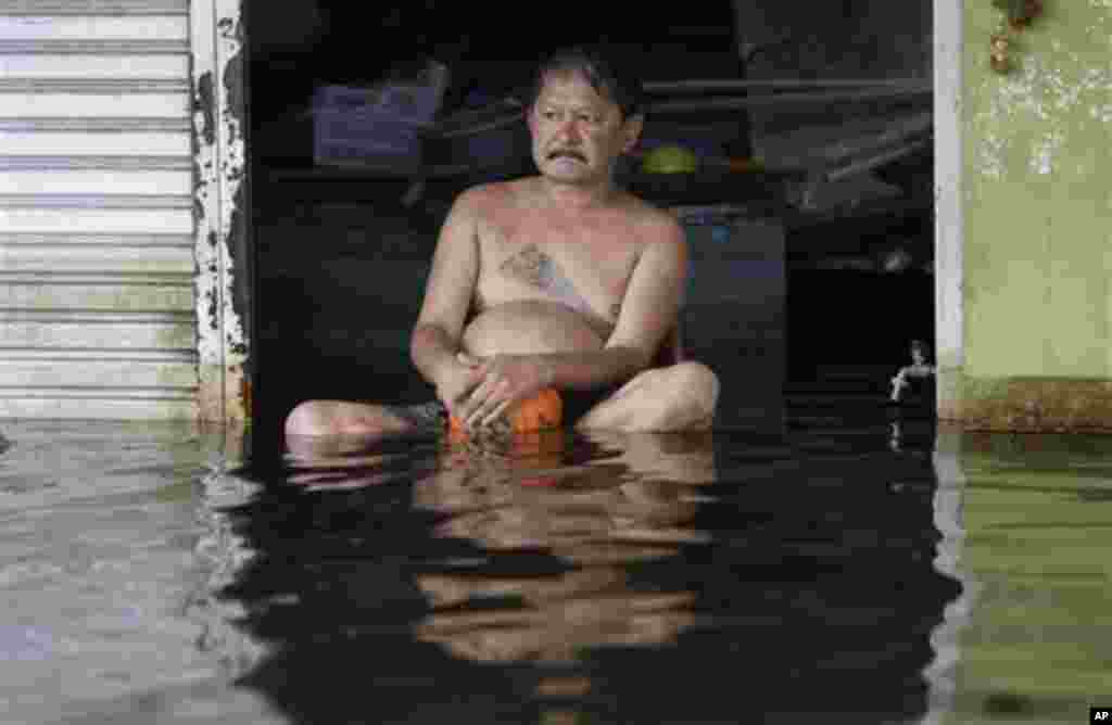 A Thai man sits outside his flooded house in Bangkok, Thailand on Wednesday Nov. 9, 2011. The flooding began in late July and the water has reached parts of Bangkok, where residents are frustrated by government confusion over how much worse the flooding w