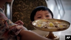FILE - A North Korean boy peeps over his serving of noodles at a restaurant in Pyongyang, Sept. 1, 2014.
