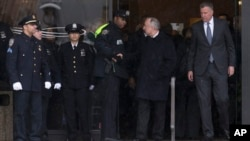 New York Police Commissioner Bill Bratton, second from right, shakes hands with an officer alongside New York City Mayor Bill de Blasio, right, as they exit the wake of Officer Wenjian Liu at Aievoli Funeral Home in Brooklyn, New York, Jan. 3, 2015.