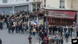 People stand in front of the restaurant Le Carillon and Le Petit Cambodge, the both establishments targeted in Friday's gun and bomb attacks, in Paris, Monday, Nov. 16, 2015. French police raided more than 150 locations overnight as authorities released the names of two more potential suicide bombers involved in the Paris attacks— one born in Syria, the other a Frenchman wanted as part of a terrorism investigation. (AP Photo/Kamil Zihnioglu)