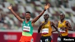 Gold medallist Selemon Barega of Ethiopia celebrates after crossing the line to win ahead of silver medallist, Joshua Cheptegei of Uganda and bronze medallist, Jacob Kiplimo of Uganda.