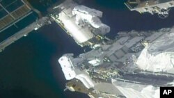 In this image taken from NASA video, NASA astronauts Kate Rubins, top, and Victor Glover work outside the International Space Station, Feb. 28, 2021.