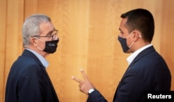 FILE - Malta's Foreign Minister Evarist Bartolo and his Italian counterpart Luigi Di Maio wear protective masks as they talk to each other during the EU foreign ministers' meeting in Berlin, Germany, Aug. 27, 2020. (Kay Nietfeld/Pool via Reuters)