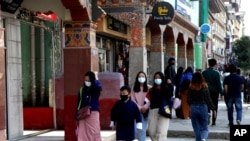 Bhutanese people wearing face masks walk through a street in Thimpu, Bhutan, as the tiny Himalayan kingdom wedged between India and China has vaccinated nearly 93% of its adult population since March 27.