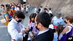 Tourists have their Green Pass checked by keepers at the entrance of the Vatican Museums, Aug. 6, 2021.