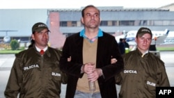 Archivo - En esta foto tomada el 13 de mayo de 2008, el exlíder paramilitar colombiano de las Autodefensas Unidas de Colombia (AUC), Salvatore Mancuso (C) alias Santander Lozada, es escoltado por policías antes de ser extraditado a EE.UU.