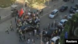 Petugas keamanan berjaga di sekeliling mobil Dubes AS Gary Locke pasca insiden kerumunan demonstran anti-Jepang. Para pengunjuk rasa tersebut melempari mobil Dubes Locke dan menghambat jalan masuk ke Kedubes AS di Beijing (18/9).