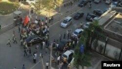 Nhân viên an ninh bao quanh xe chở Đại sứ Mỹ Gary Locke sau khi người biểu tình chống Nhật Bản tìm cách ngăn chặn xe cộ bên ngoài Đại sứ quán Mỹ tại Bắc Kinh hôm 18/9/2012. Hình chụp từ video do nhà bất đồng chính kiến Ngải Vị Vị quay được.