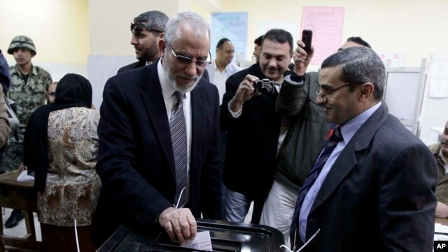 Muslim Brotherhood leader Mohamed Badie, second right, waits in line outside a polling place in Beni Suef, Egypt, to vote on a constitution drafted by supporters of President Mohamed Morsi, Dec. 22, 2012.