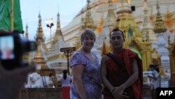 Khách du lịch chụp hình với một tu sĩ Phật giáo tại chùa Shwedagon ở Yangon.