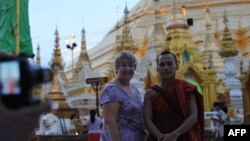 A western tourist poses for a photograph with a Buddhist monk at the Shwedagon Pagoda in Rangoon, Burma, May 31, 2012.