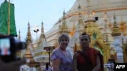Một du khách chụp ảnh với một tu sĩ Phật giáo tại chùa Shwedagon ở Rangoon, Miến Điện