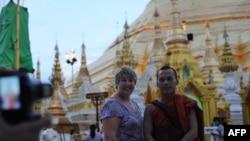 Seorang wisatawan berfoto bersama seorang biksu di Pagoda Shwedagon di Ranggon, Burma (Foto: dok). Arus wisatawan manca negara ke Burma mulai meningkat sejak tahun 2011.