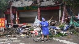 Seorang warga membawa sepedanya di antara rumah yang rusak akibat gempa di Luzhou, provinsi Sichuan, China, Kamis 16 September 2021.