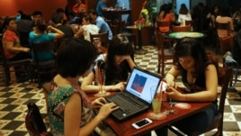 FILE - Three young Vietnamese girls use a laptop and smart phones to go online at a cafe in Ha Noi, Vietnam, May 14, 2013.