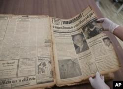 Seorang karyawan di Perpustakaan Nasional menunjukkan halaman depan surat kabar Daily Mail edisi Senin, Februari 1958 yang memperlihatkan pembunuh berantai terkenal Si Ouey di Bangkok, Thailand, Senin, 9 Juli 2019.