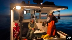 Virginia Oliver, left, chats with her son Max Oliver while heading out to sea to fish for lobster at dawn, Tuesday, Aug. 31, 2021, off Rockland, Maine. (AP Photo/Robert F. Bukaty)