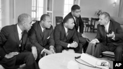 U.S. President Lyndon B. Johnson, right, talks with civil rights leaders in his White House office in Washington, D.C., Jan. 18, 1964. The black leaders, from left, are, Roy Wilkins, executive secretary of the National Association for the Advancement of Colored People (NAACP); James Farmer, national director of the Committee on Racial Equality; Dr. Martin Luther King Jr., head of the Southern Christian Leadership Conference; and Whitney Young, executive director of the Urban League. (AP Photo)