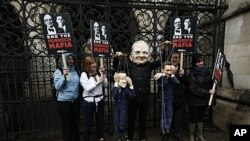 Protester wears a Rupert Murdoch mask, holds puppets of British PM David Cameron, left, and Culture Secretary Jeremy Hunt, outside Lord Justice Brian Leveson's inquiry, High Court, London, April 25, 2012.