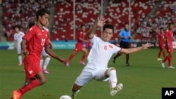 Nguyen Minh Tung of Vietnam (6) tackles Kyaw Zin Lwin of Myanmar in the soccer semi-final at the SEA Games in Singapore Saturday, June 13, 2015. (AP Photo/Joseph Nair)
