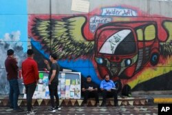 In this Sunday, Nov. 17, 2019 photo, protesters read donated books in front of graffiti, at the Saadoun Tunnel, in Baghdad, Iraq. The tunnel that passes under Baghdad's landmark Tahrir Square has become an ad hoc museum for Iraq's revolution: Young artist