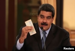 Venezuela's President Nicolas Maduro holds a bank note from the new Venezuelan currency Bolivar Soberano (Sovereign Bolivar), as he speaks during a meeting with ministers at Miraflores Palace in Caracas, Aug. 17, 2018.