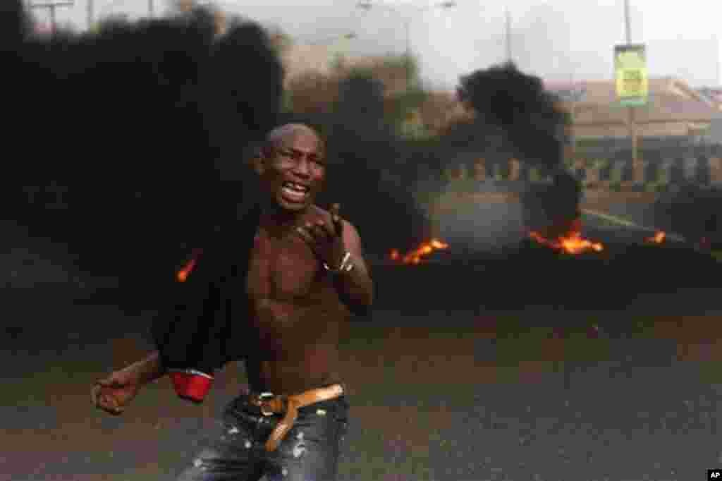A angry youth protest in front of a burning barrier following the removal of a fuel subsidy by the government in Lagos, Nigeria, Tuesday, Jan. 10, 201. Angry youths erected a burning roadblock outside luxury enclaves in Nigeria's commercial capital Tuesda