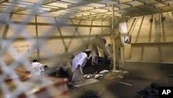 透过铁丝网可看到巴格拉姆空军基地附近的伯尔万羁押中心内的囚犯在做午间祷告。
