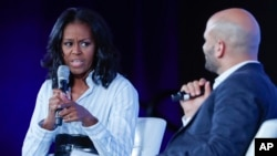 Former first lady Michelle Obama talks with Sam Kass, former White House chef and senior policy adviser for nutrition, at the Partnership for a Healthier America 2017 Healthier Future Summit in Washington, May 12, 2017