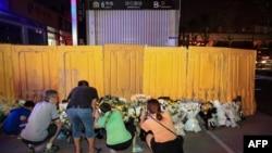 在黃色欄板被拆除前,鄭州市民前往地鐵5號線沙口路站口獻花悼念水災死難者。(2021年7月26日)