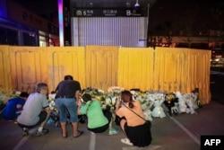 河南鄭州市民在被黃色圍欄圍起來的地鐵5號線車站前獻花悼念水災死難者。(2021年7月26日)