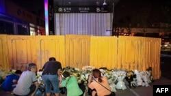 河南鄭州市民在被黃色圍欄圍起來的地鐵5號線車站前獻花悼念水災死難者。 (2021年7月26日)