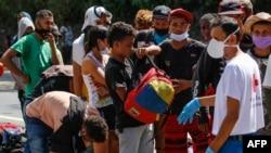 Migrantes venezolanos usan mascarilla mientras hacen cola para recibir alimentos y medicamentos de miembros de la Cruz Roja en una carretera en Cúcuta, Colombia, en la frontera con Venezuela, el 2 de febrero de 2021.