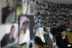 FILE - Bosnian women watch a TV broadcast of Bosnian Serb leader Milorad Dodik, testifying in Radovan Karadzic's defense at The Hague, in Tuzla, Bosnia, April 9, 2013.