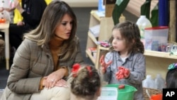 First lady Melania Trump watches as children form objects from Play-Doh at Joint Base Elmendorf-Richardson, Alaska, Nov. 10, 2017.
